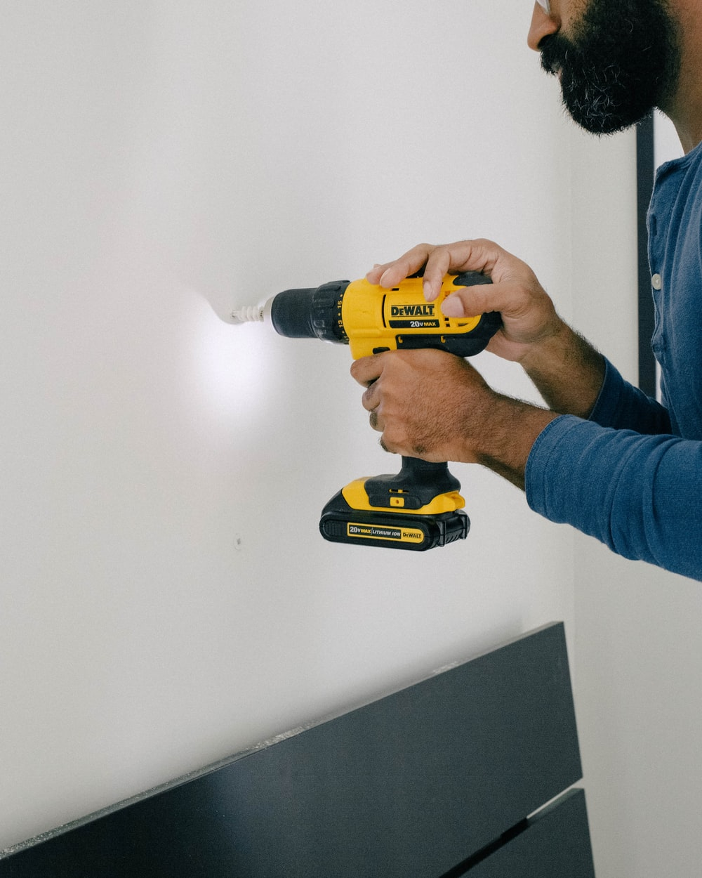 person holding yellow and black cordless hand drill