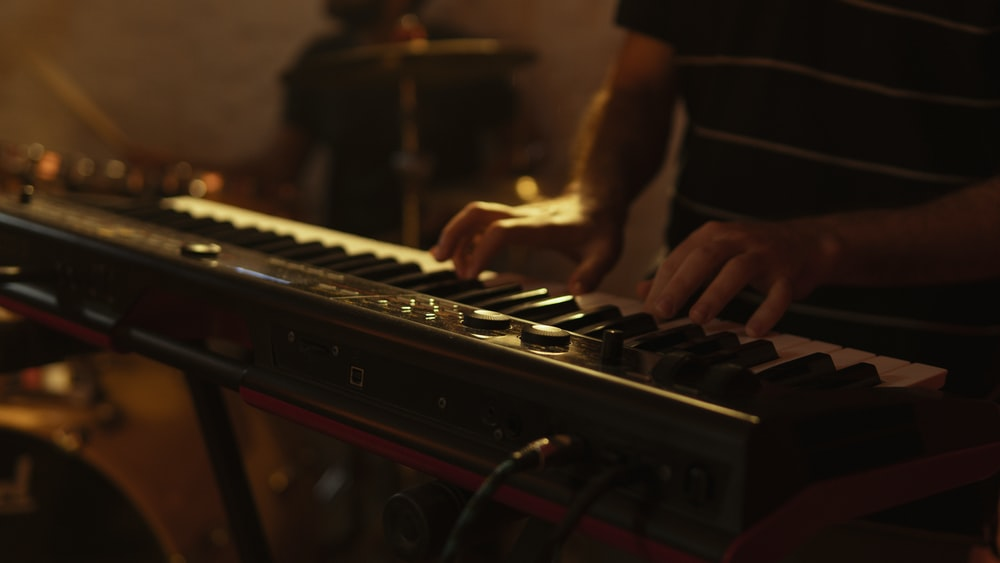 person playing brown and black electric piano