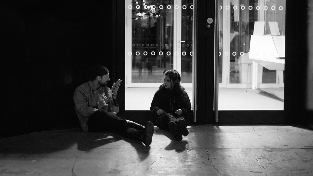 man and woman sitting on floor in grayscale photography
