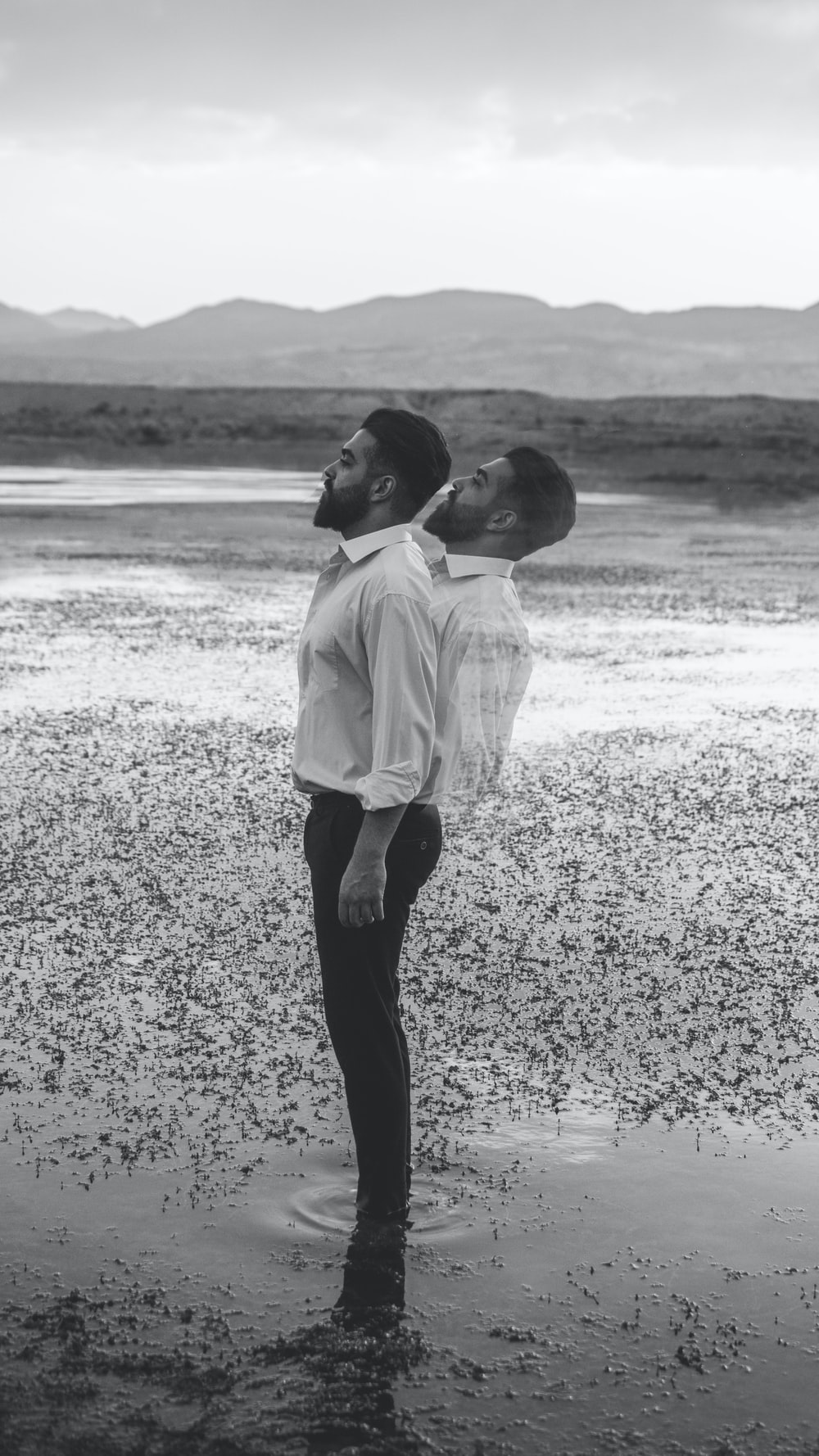 boy in white dress shirt and black pants walking on seashore during daytime