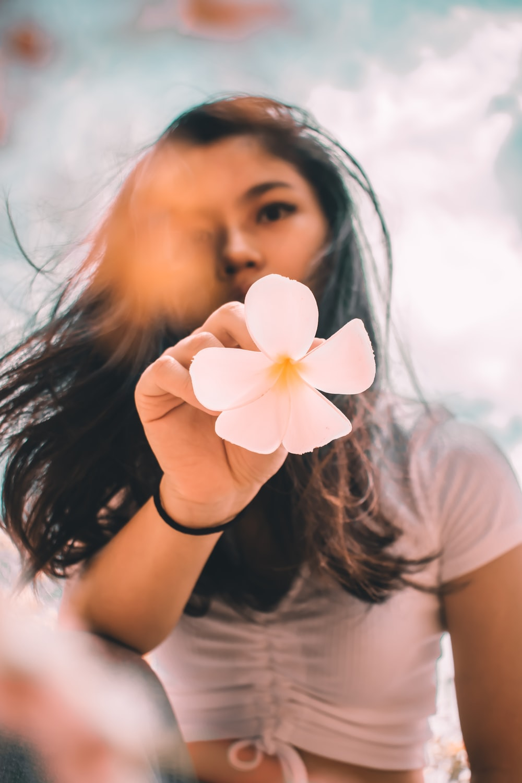woman in white shirt holding white flower