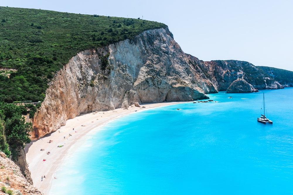 green mountain beside blue sea during daytime