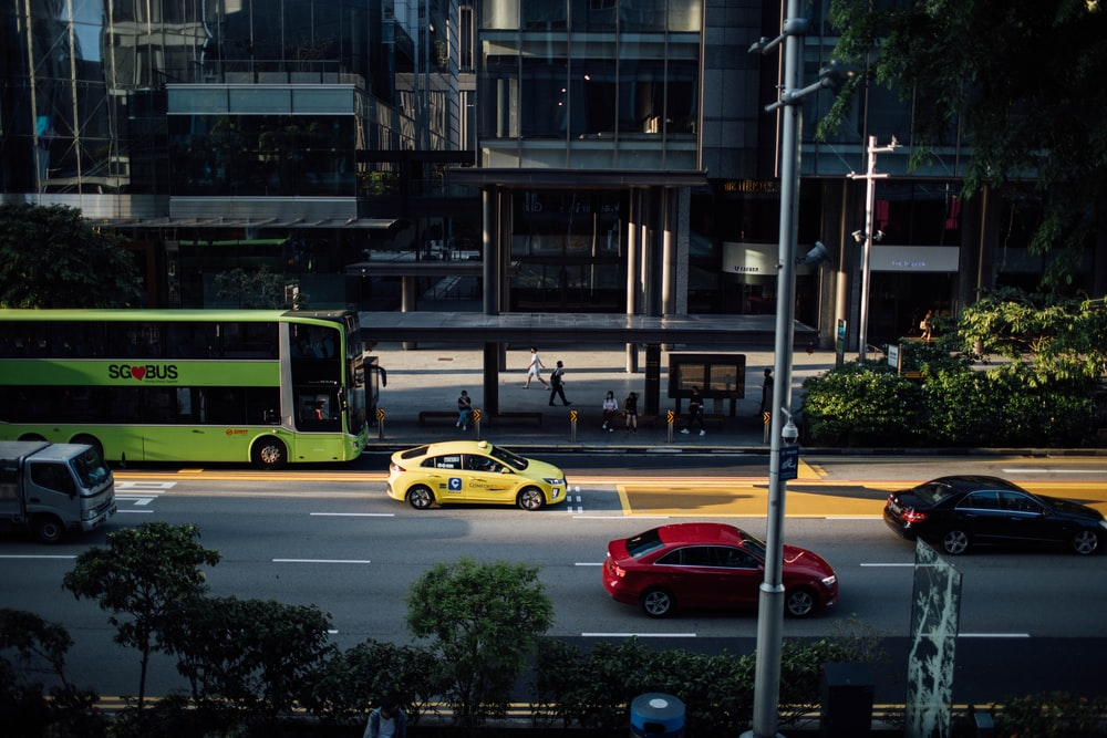 yellow and black cars on road near building during daytime