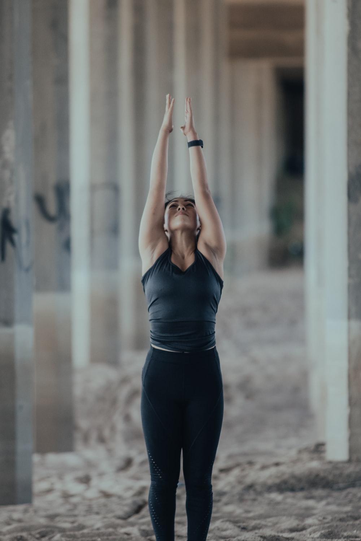 woman in blue tank top and black leggings doing yoga