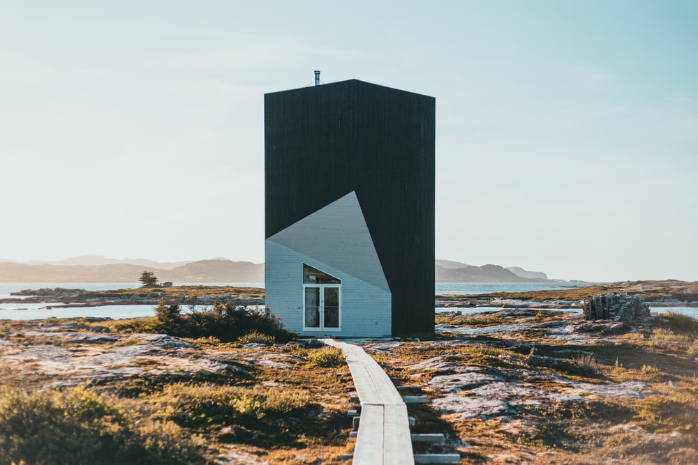 black and white wooden house on brown field during daytime