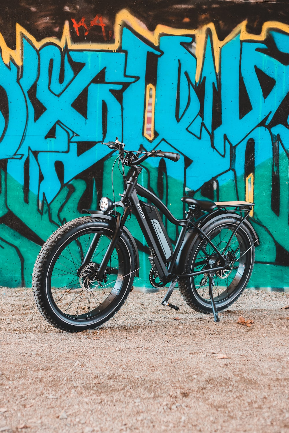 black and gray mountain bike leaning on wall with graffiti