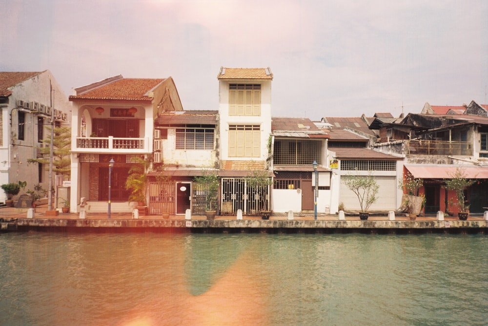 white and brown concrete building beside body of water during daytime