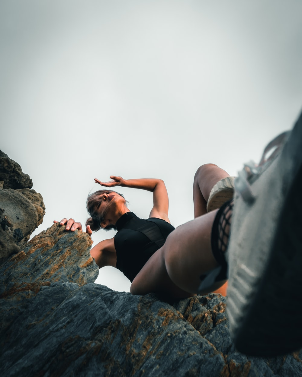 woman in black tank top and black shorts lying on rock