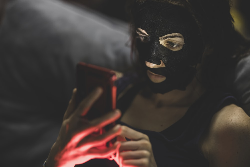 woman in black mask holding red smartphone