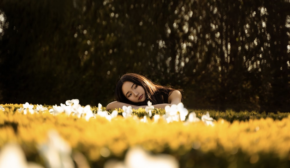 woman in white tank top lying on yellow flower field during daytime