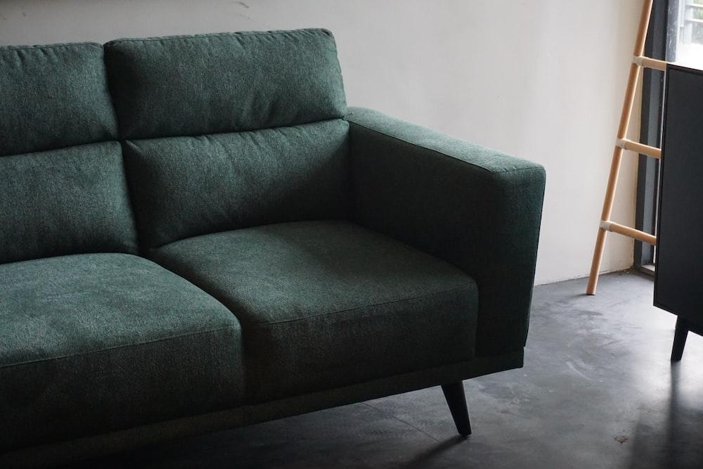 gray cushion armchair beside white wall