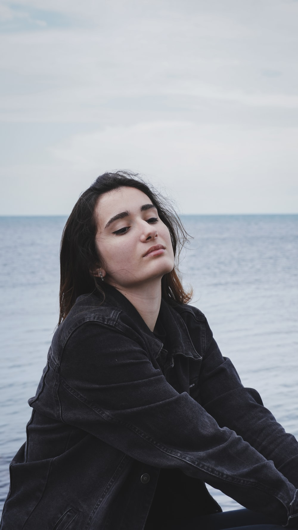 woman in black jacket standing near sea during daytime