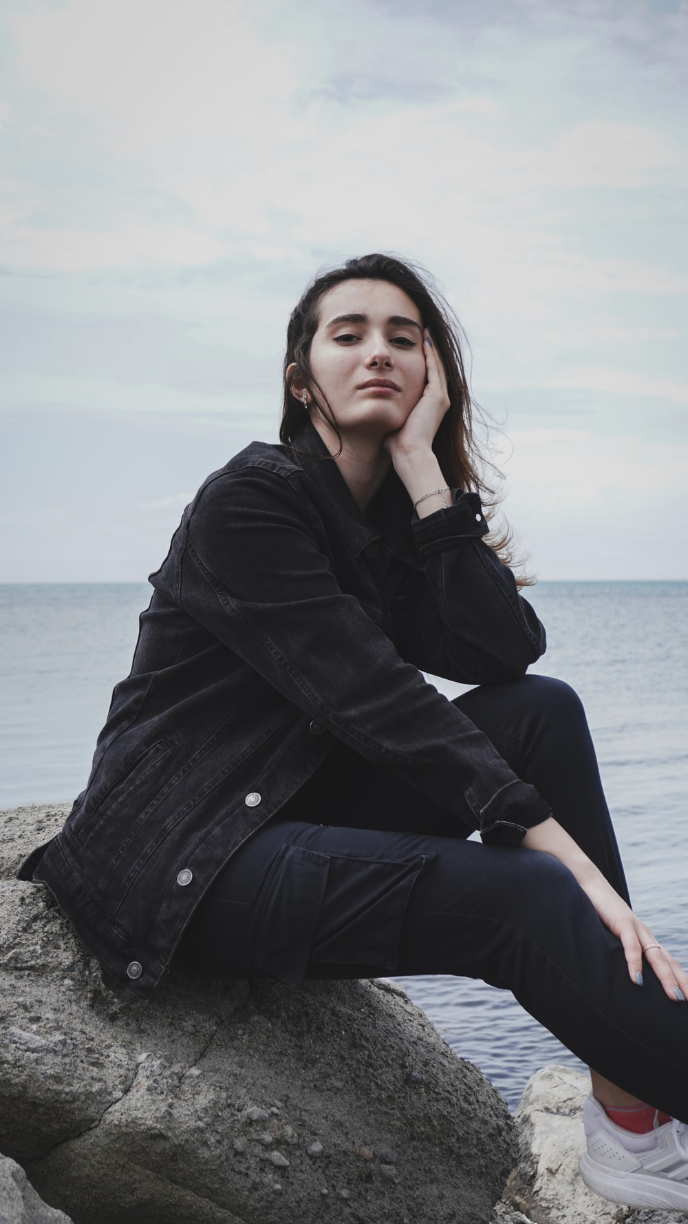 woman in black coat sitting on rock near sea during daytime