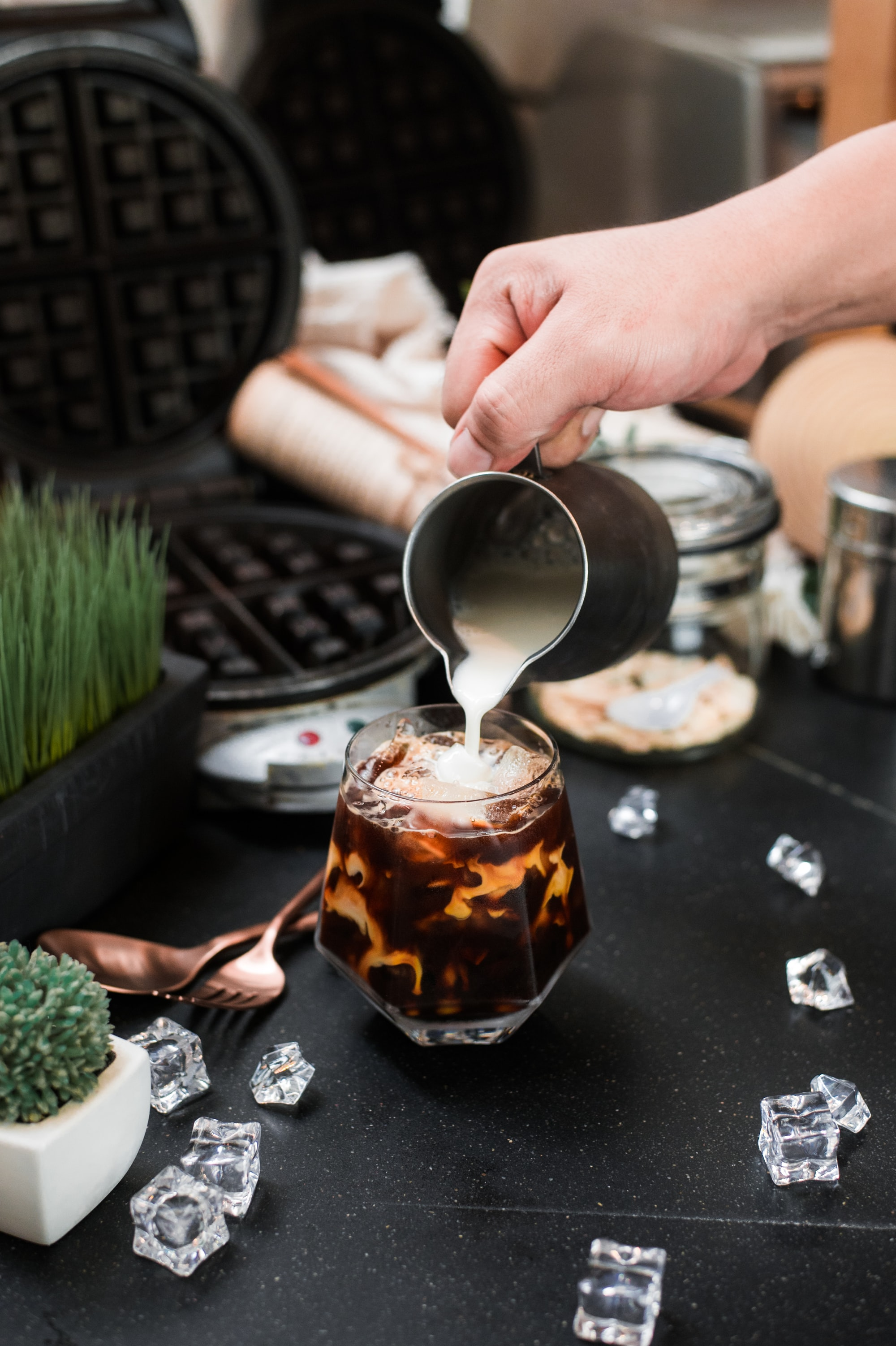 Barista pouring milk into a glass of iced coffee