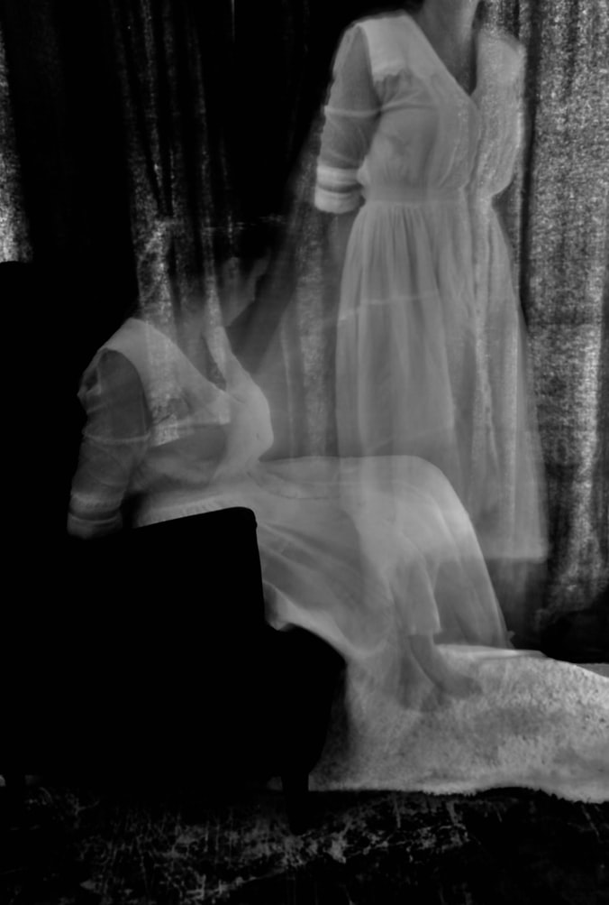 Black and white Exposure of a woman in a white dress on a couch