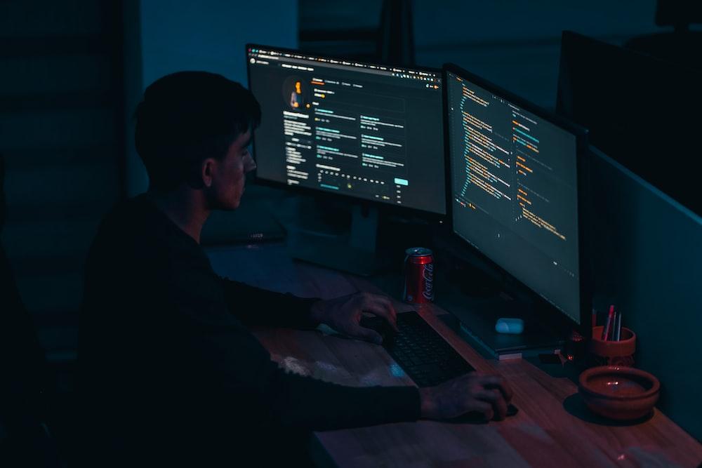 man in black long sleeve shirt using computer