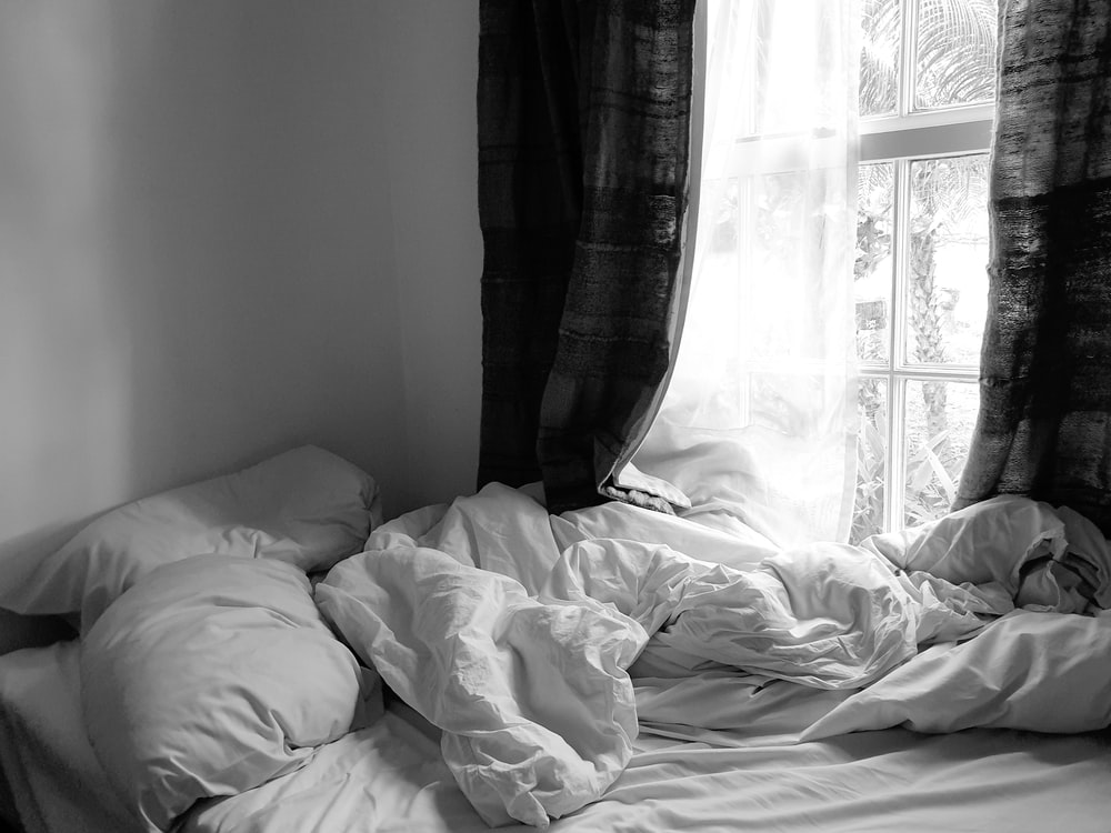 grayscale photo of bed with white blanket