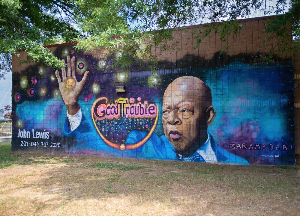 man in blue shirt standing near wall with graffiti