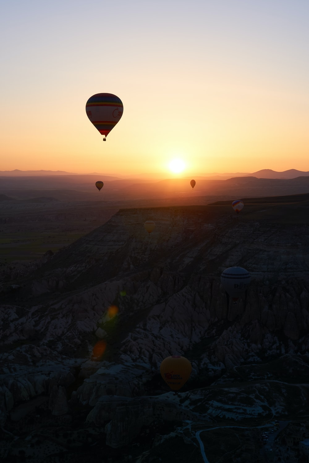 hot air balloons flying over the mountains during sunset