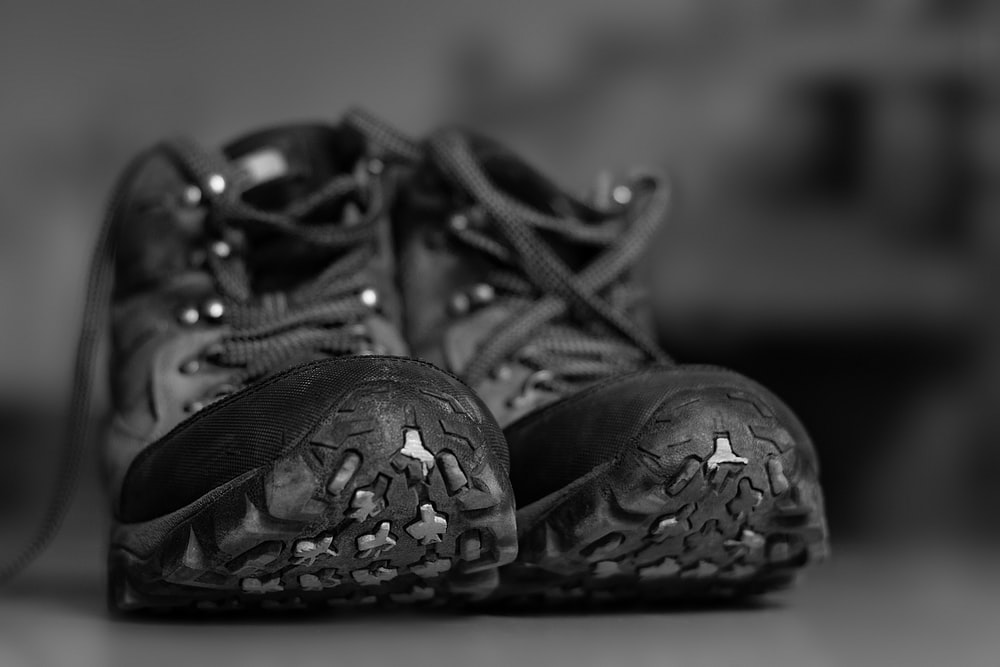 grayscale photo of black and white sneakers