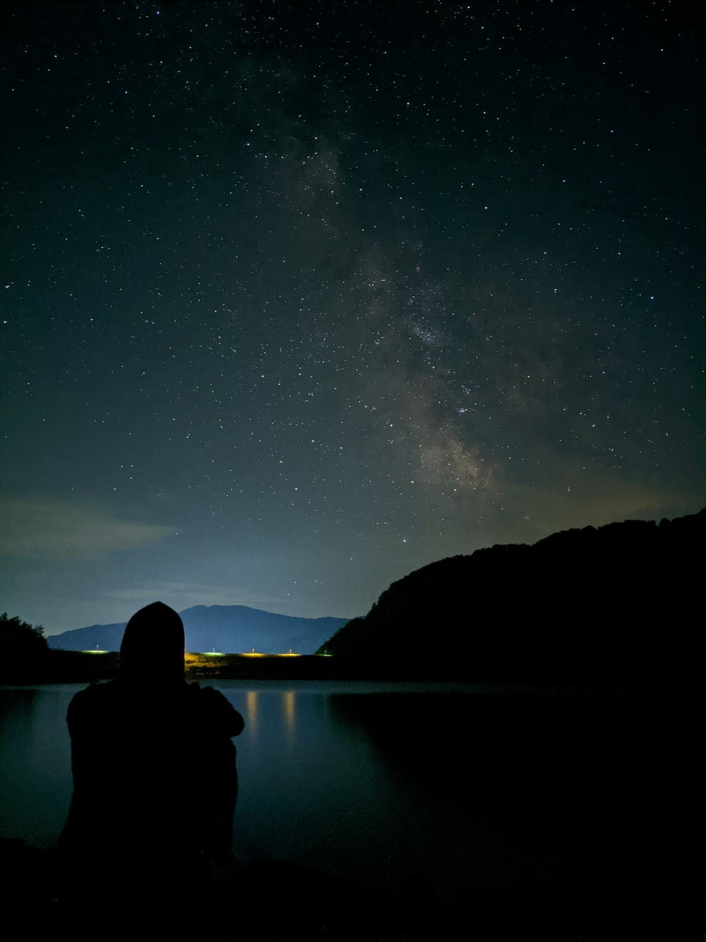 silhouette of person sitting on rock near body of water during night time