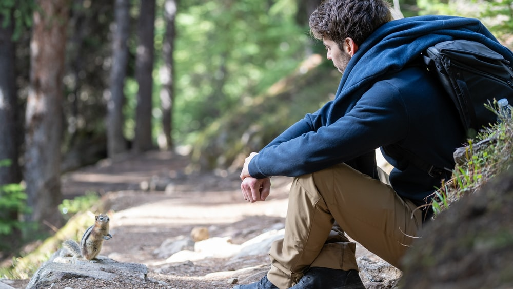 man in blue hoodie and brown pants sitting on gray rock during daytime