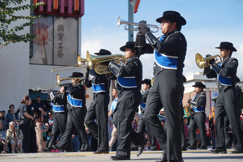 people in black and blue uniform playing musical instruments during daytime