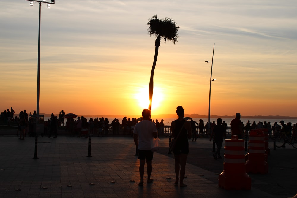 people walking on the street during sunset