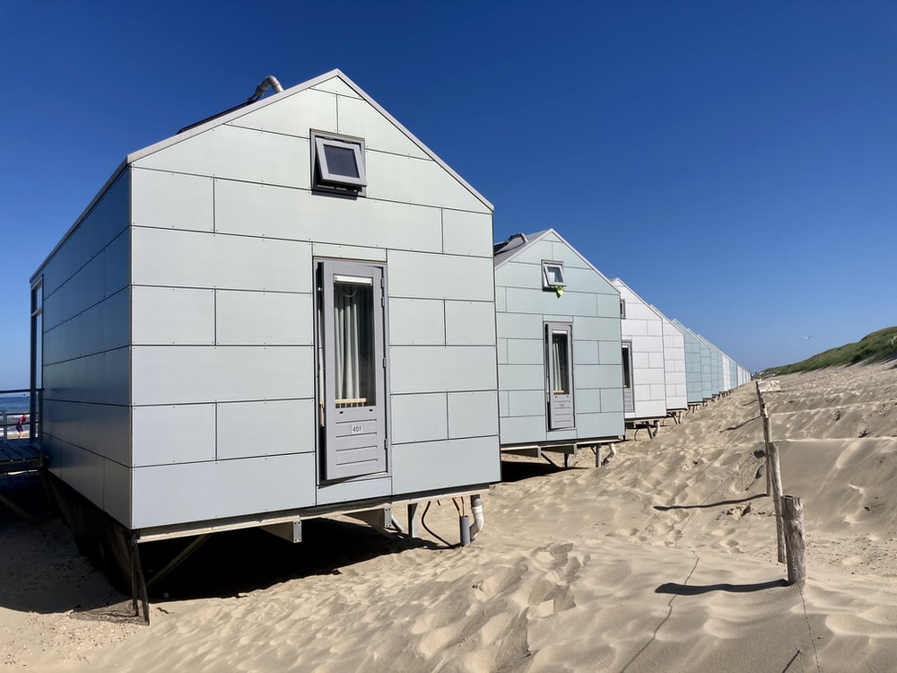 white concrete house on brown sand under blue sky during daytime
