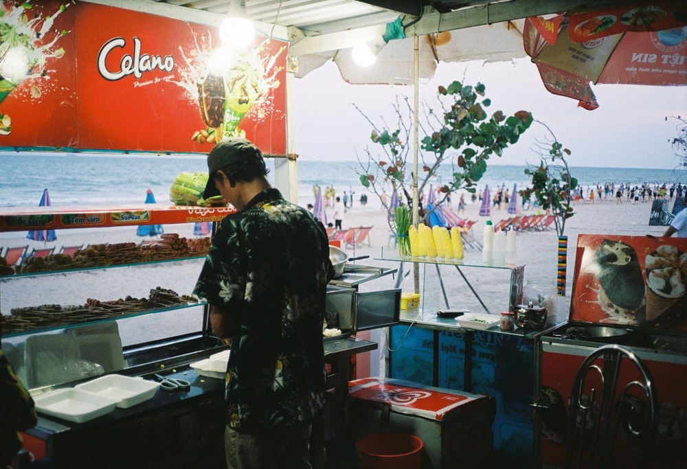 woman in black and white floral dress standing in front of food stand