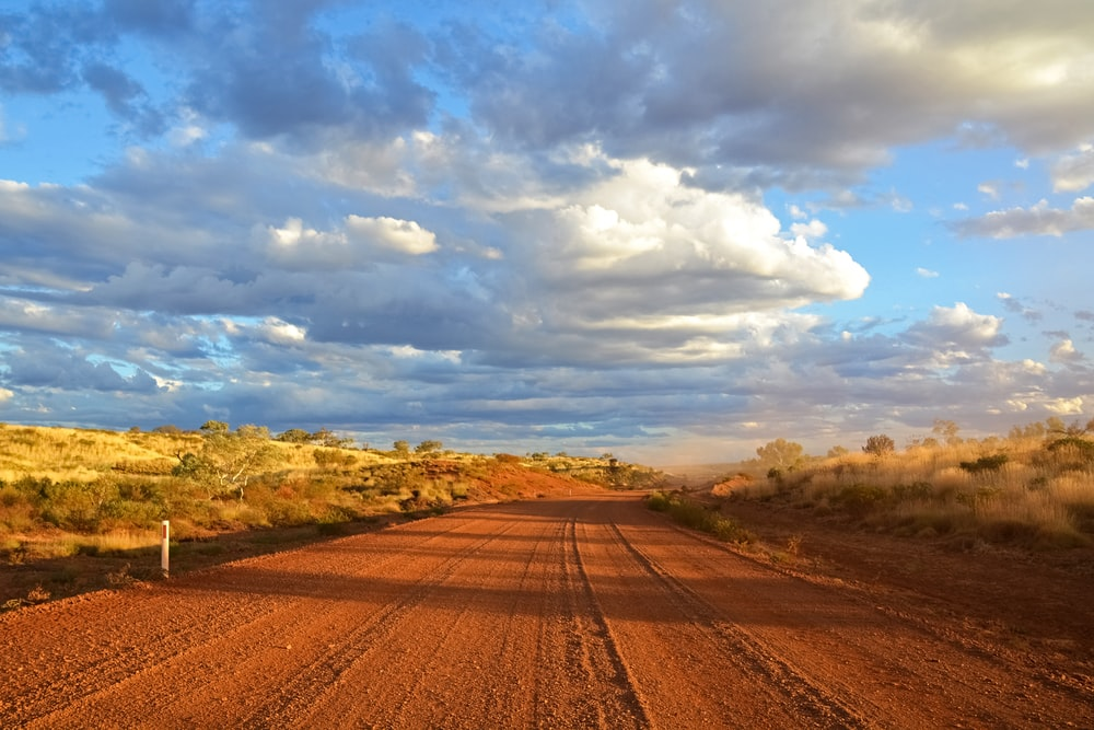 brown dirt road under blue sky and white clouds during daytime