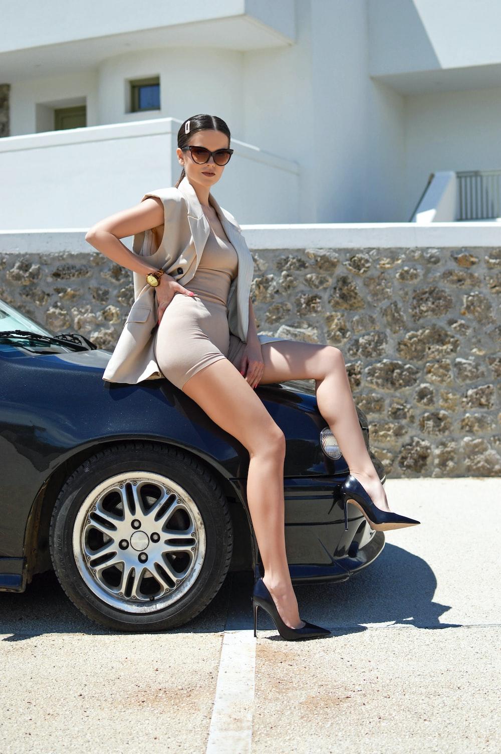 woman in white bikini sitting on black car