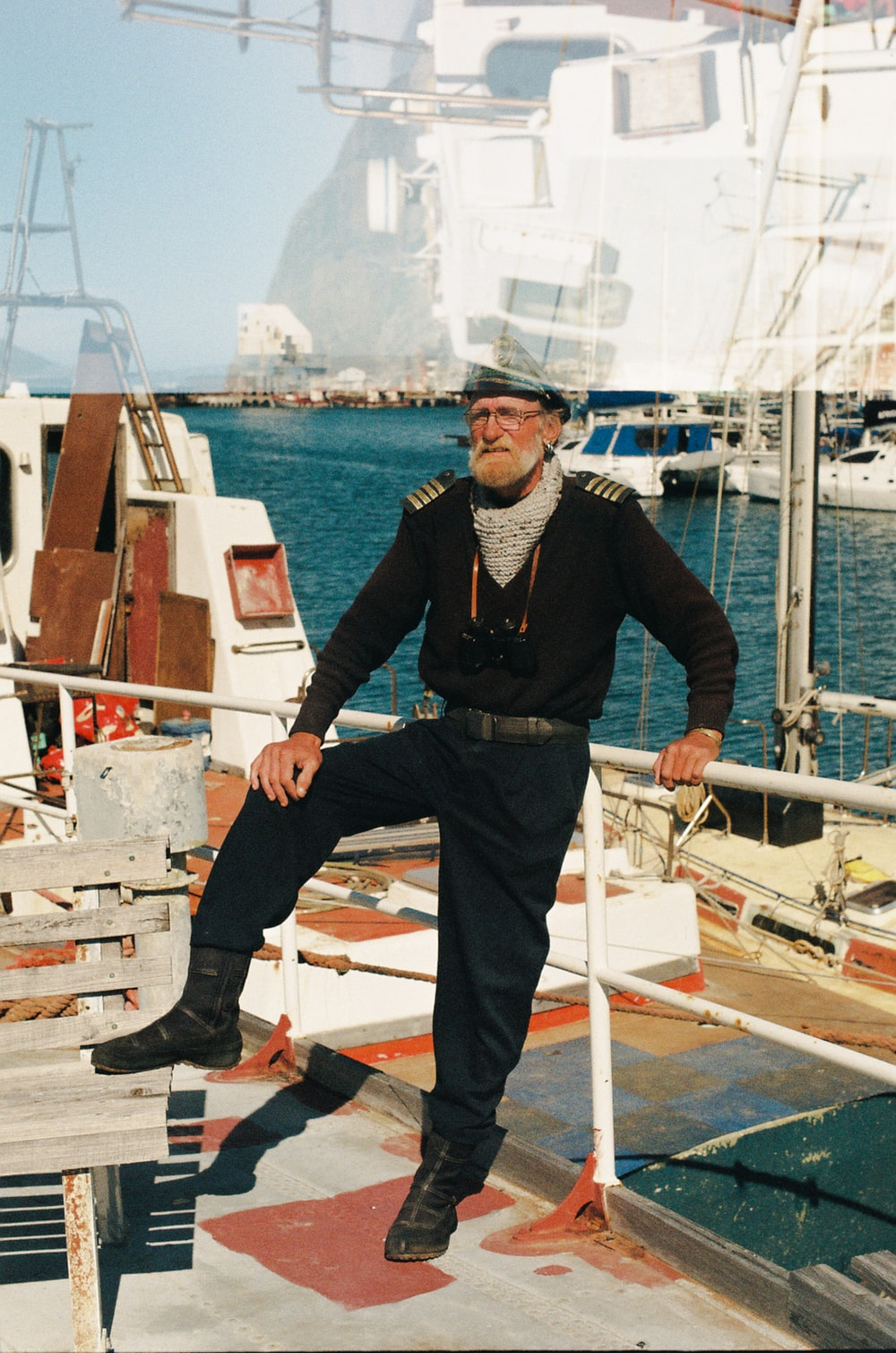 man in black jacket and blue denim jeans standing on white boat during daytime