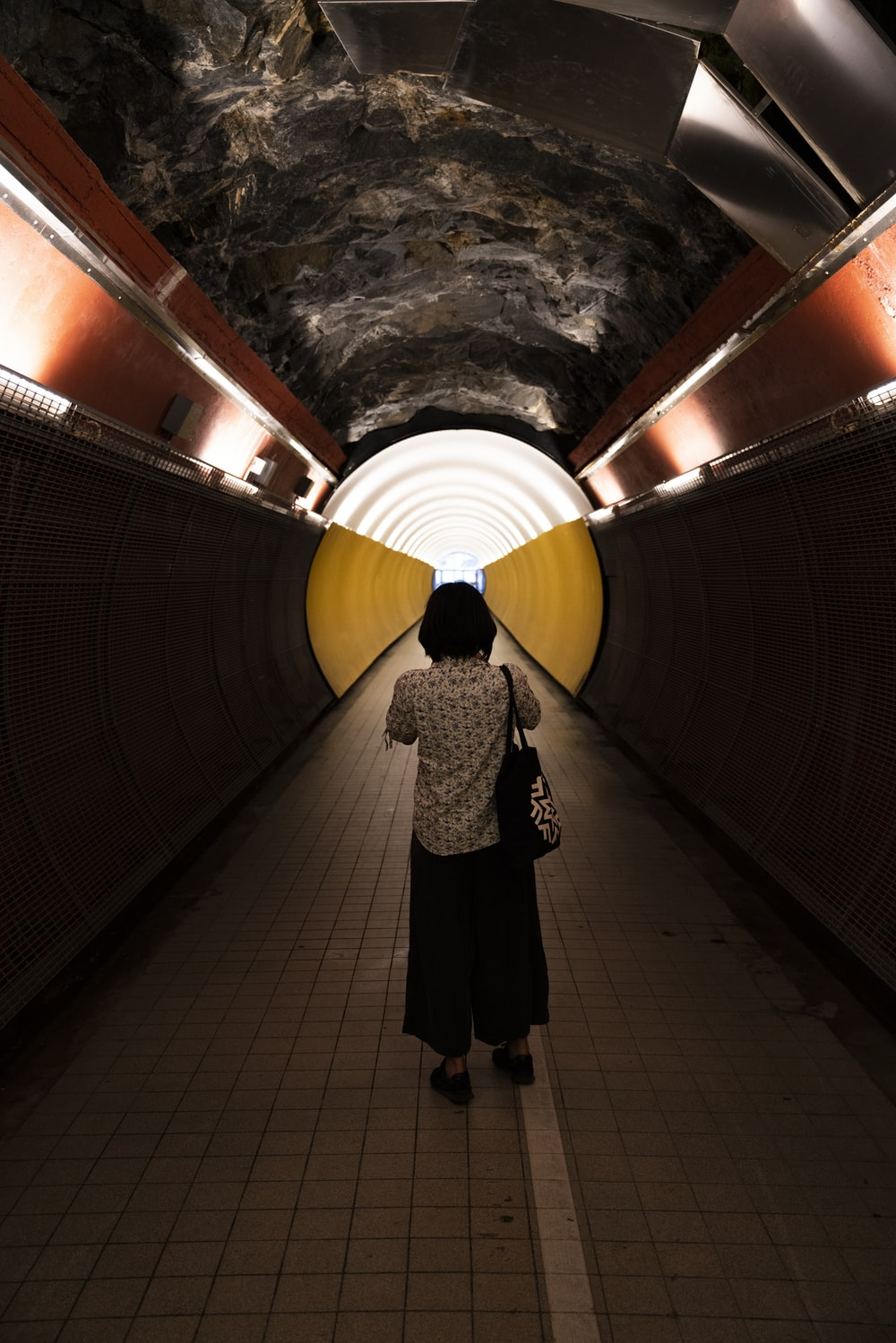 woman in black and white coat standing on tunnel