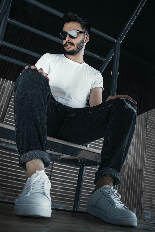 man in white crew neck t-shirt and black pants sitting on black metal bench