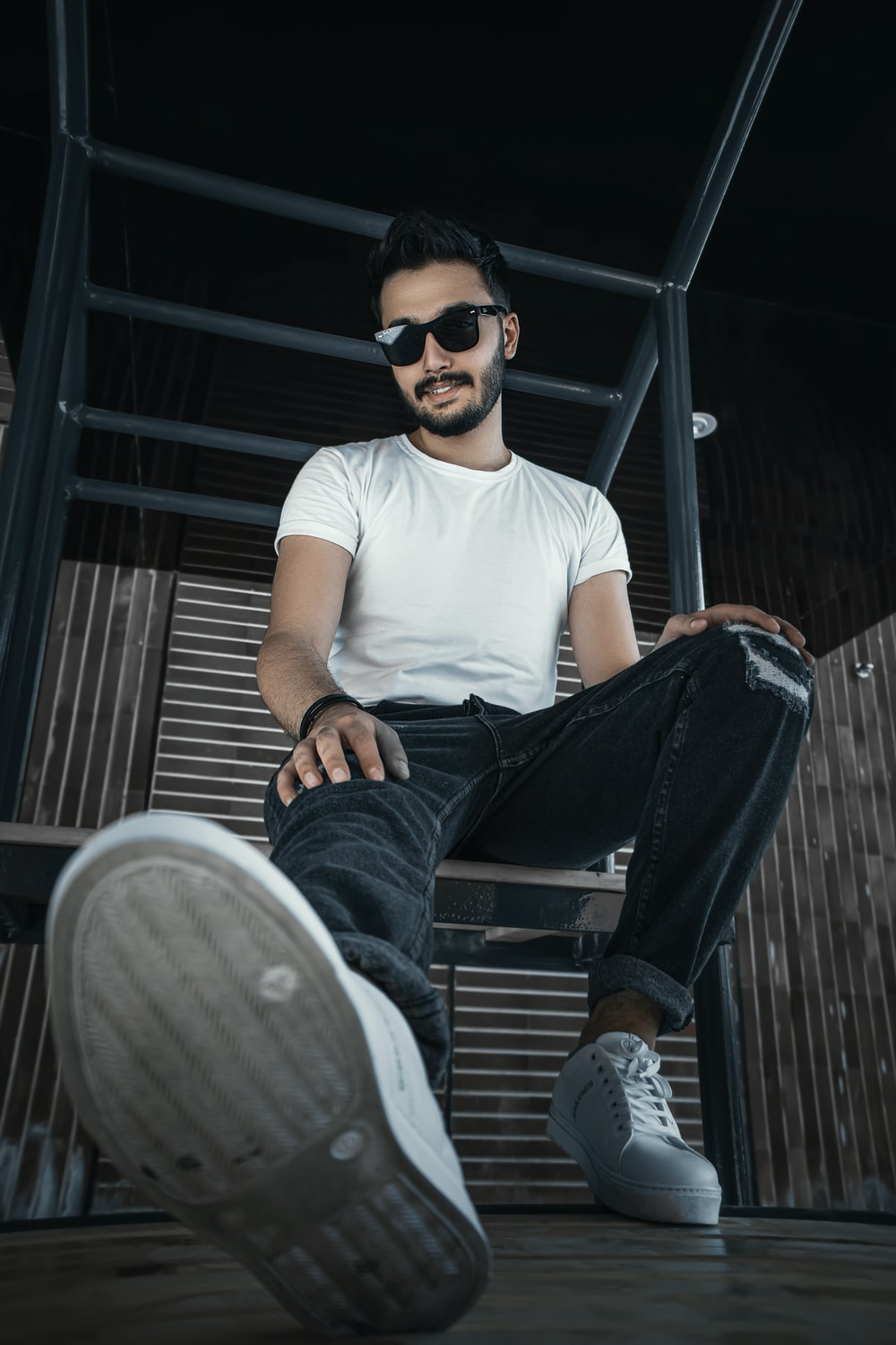 man in white crew neck t-shirt and blue denim jeans sitting on gray wooden bench