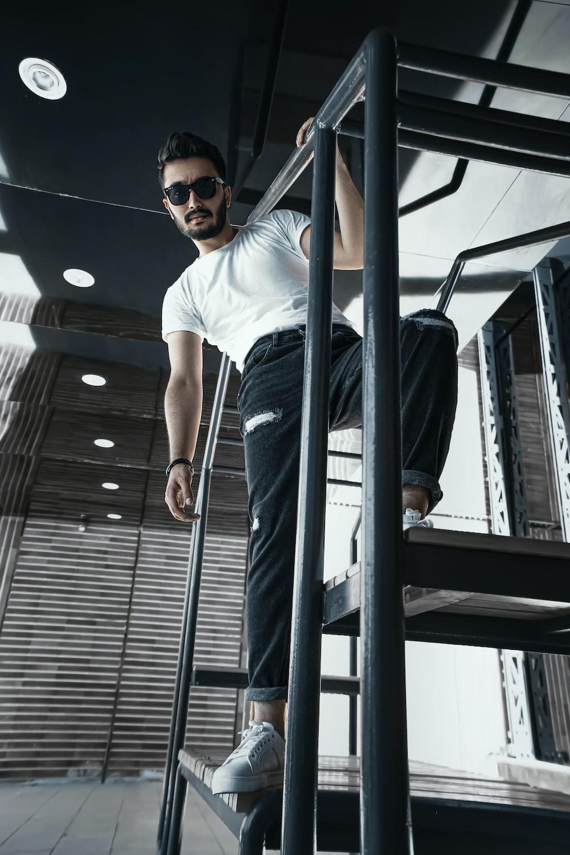 man in white crew neck t-shirt wearing black sunglasses standing beside gray metal railings