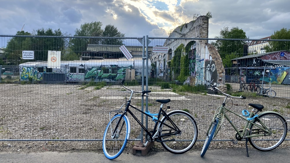 blue and black mountain bike parked beside gray metal fence during daytime