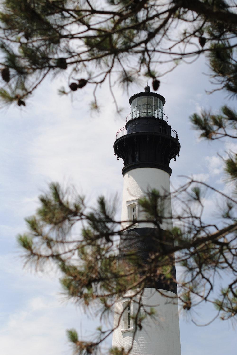 white and black lighthouse under blue sky during daytime