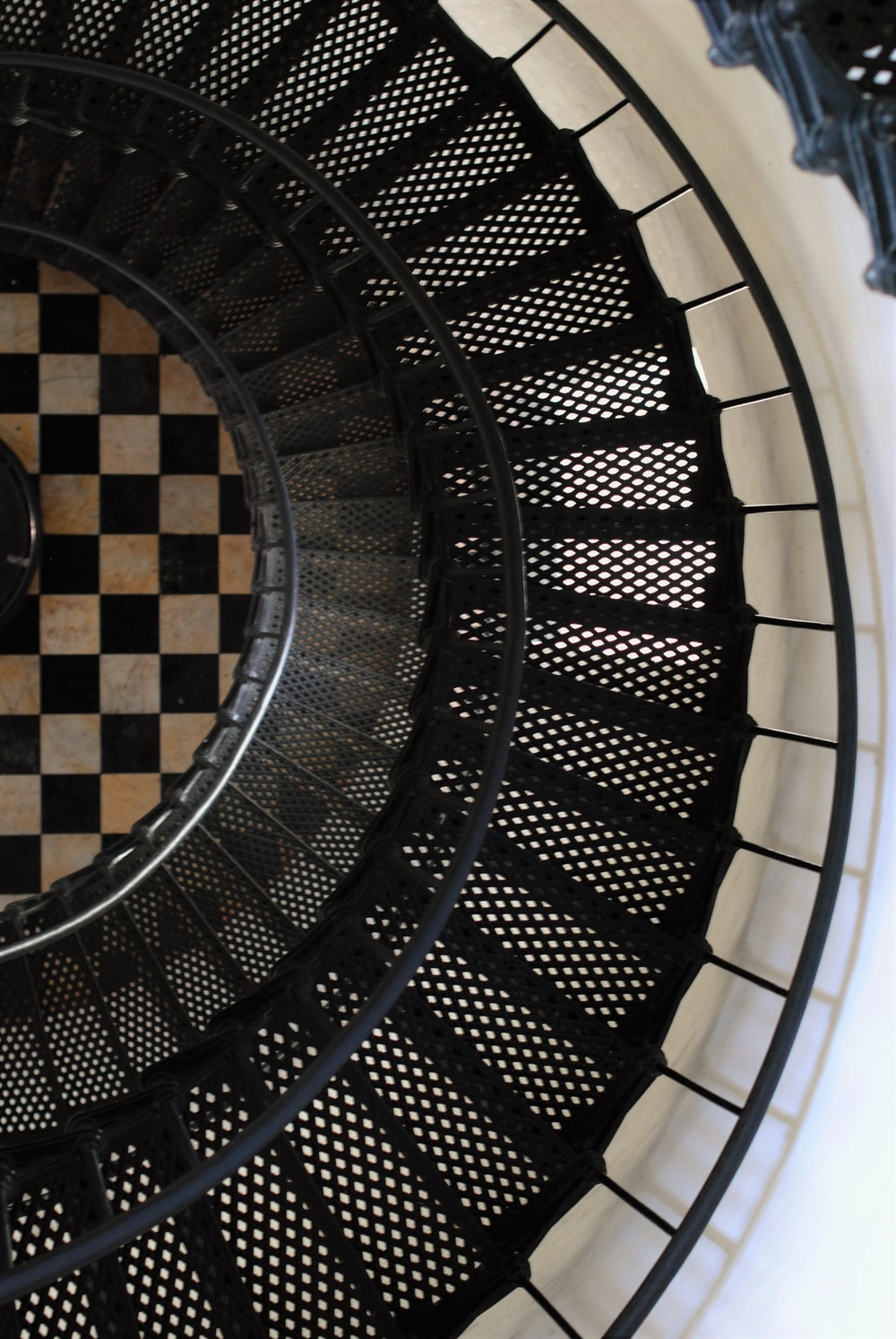 man in black jacket standing on spiral staircase