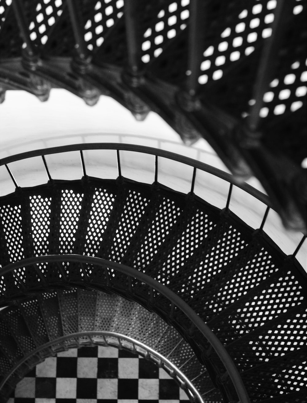 black metal spiral staircase in grayscale photography