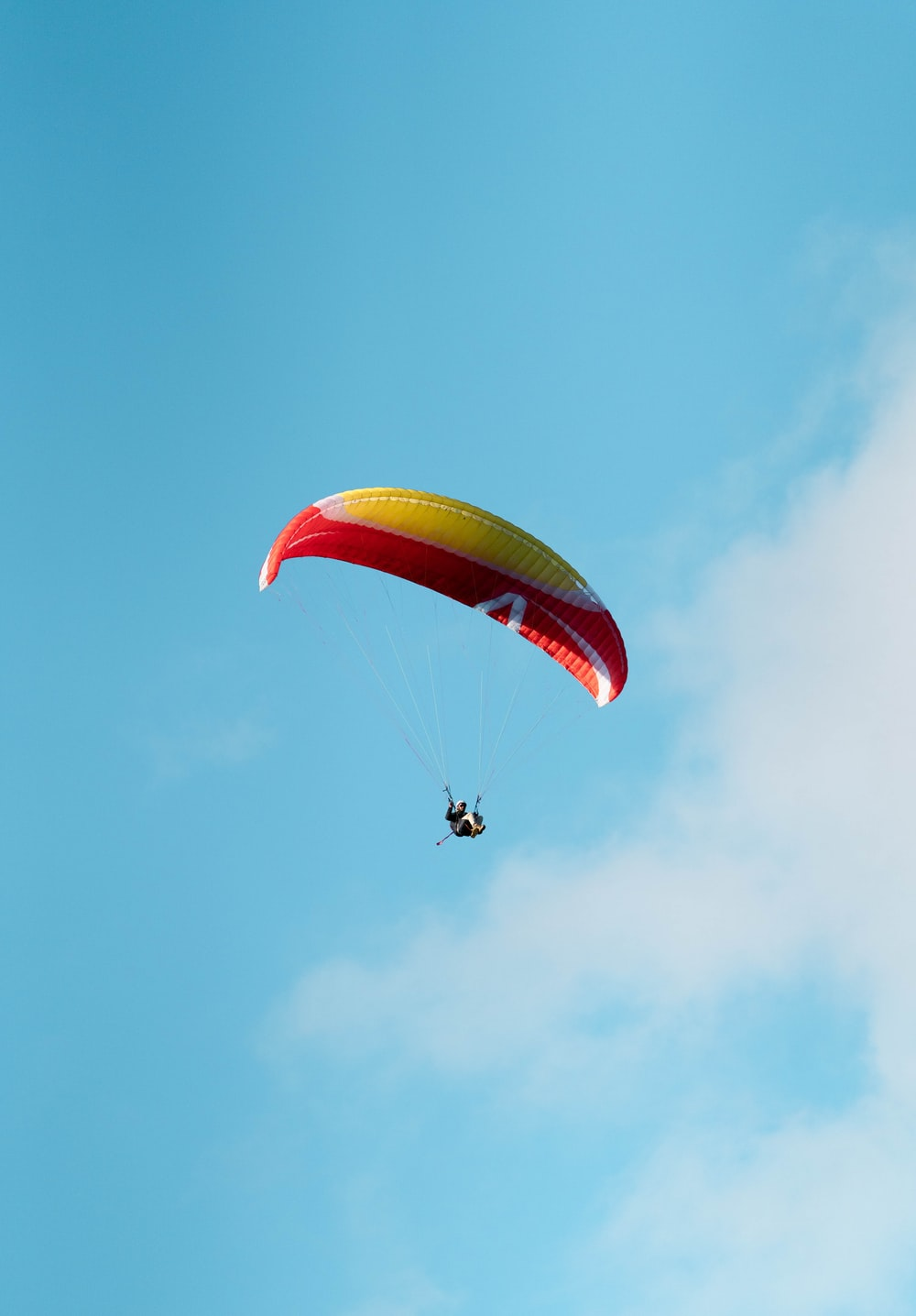 person in red and yellow parachute