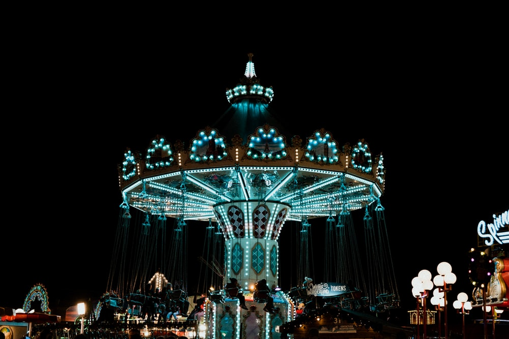 people standing near white and blue lighted carousel during night time