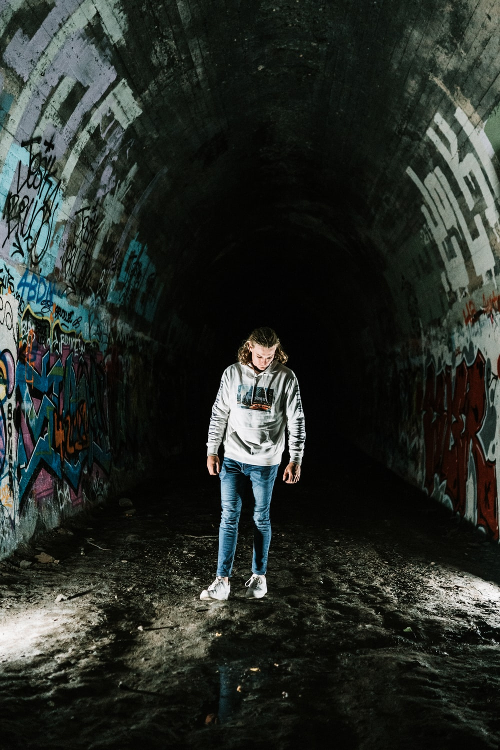 man in black and white jacket and blue denim jeans walking on tunnel