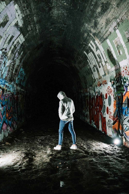 man in gray hoodie walking on tunnel