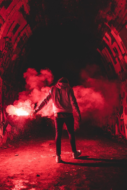 man in black hoodie standing on red light