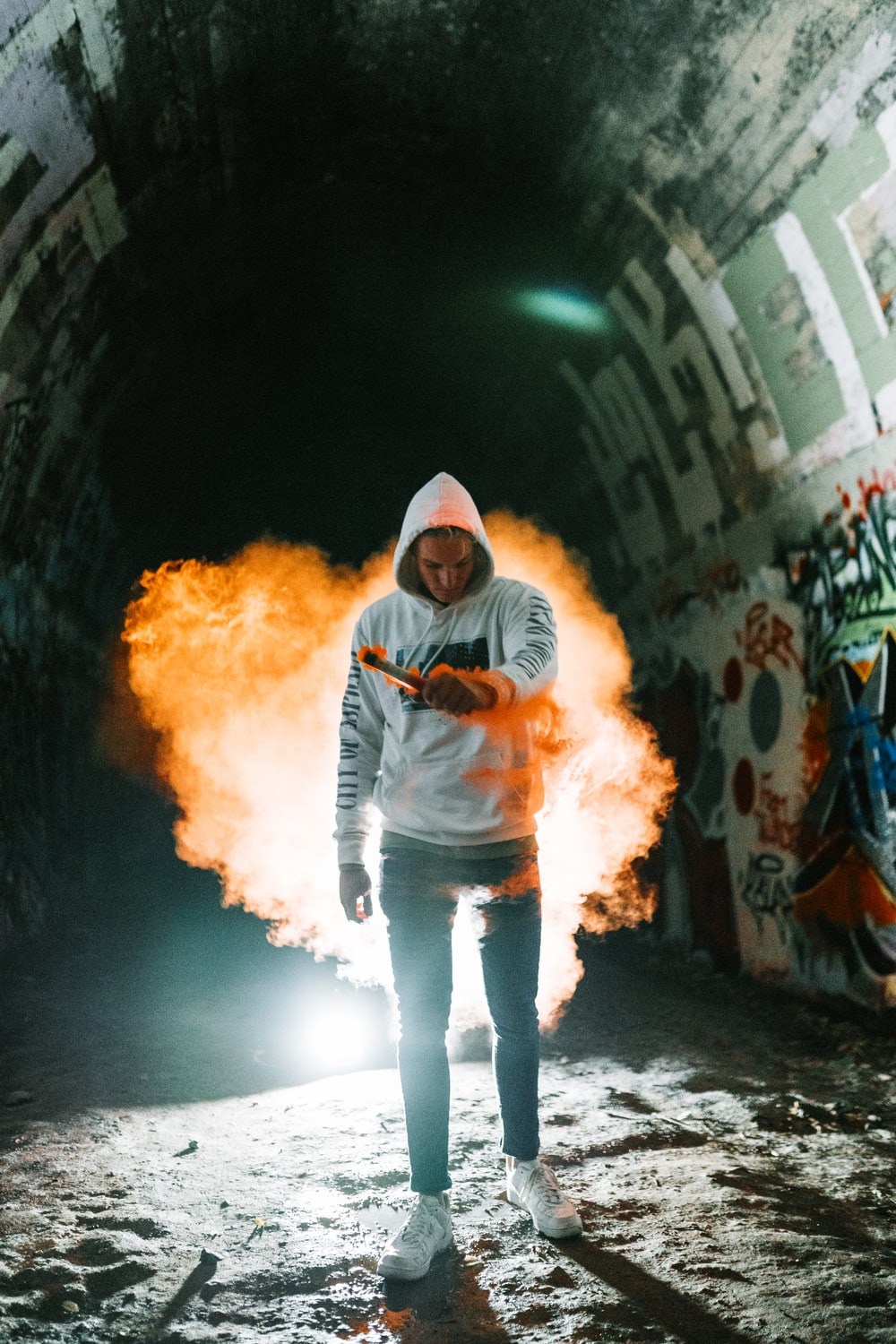 man in black and gray hoodie standing on tunnel with fire