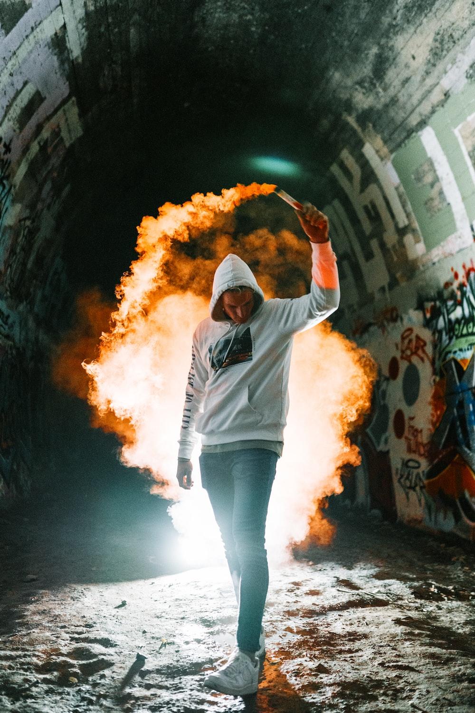 man in white hoodie and blue denim jeans holding orange powder