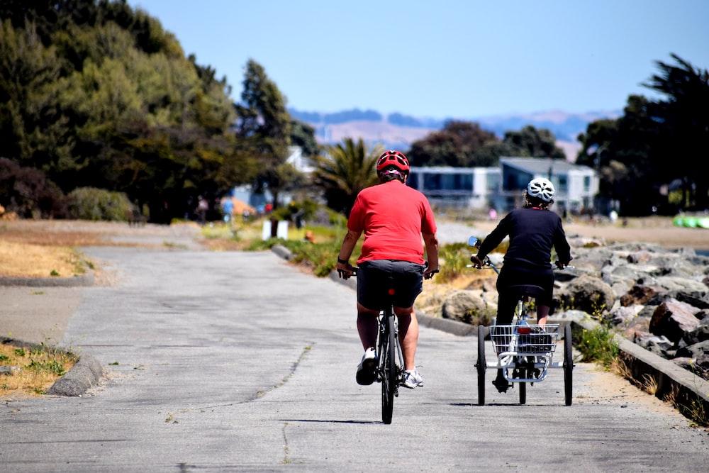 man in red shirt riding bicycle during daytime
