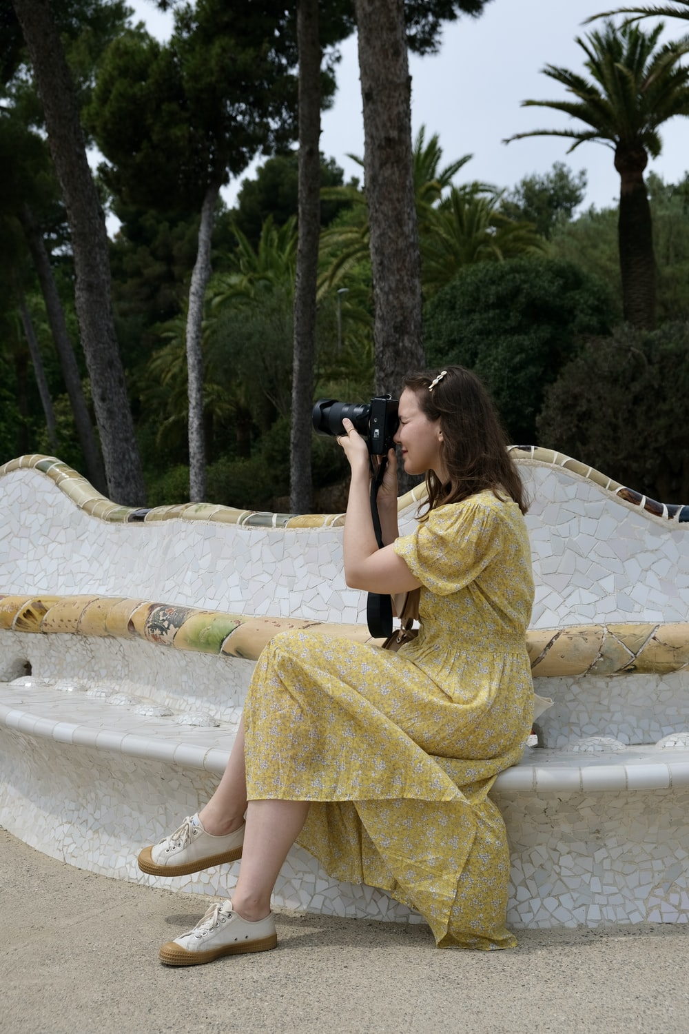 woman in yellow dress taking photo of green trees during daytime